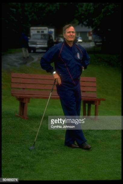Pres Bush determinedly enjoying his vacation despite gulf crisis leaning jauntily on his club out on golf course in Kennebunkport ME