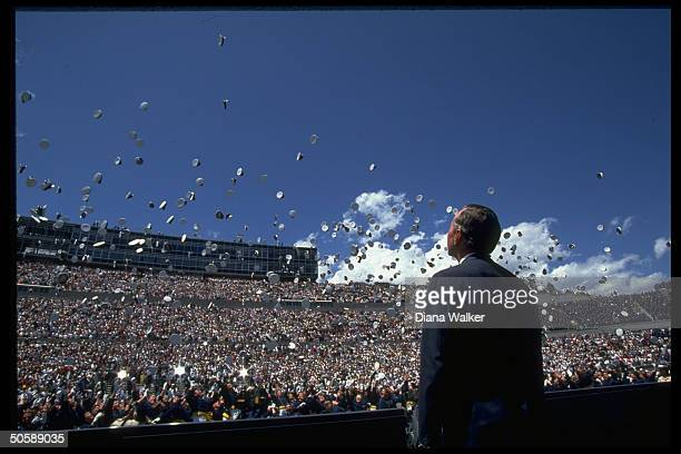 Pres Bush enjoying spectacle of caps soaring upwards en masse tossed by graduates at Air Force Academy Falcon Stadium commencement