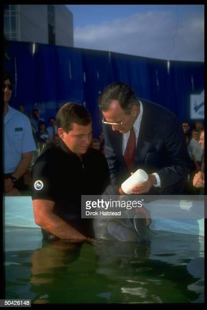 Pres Bush feeding aquatic animal held by Sea World staffer fr baby type bottle during stay in FL