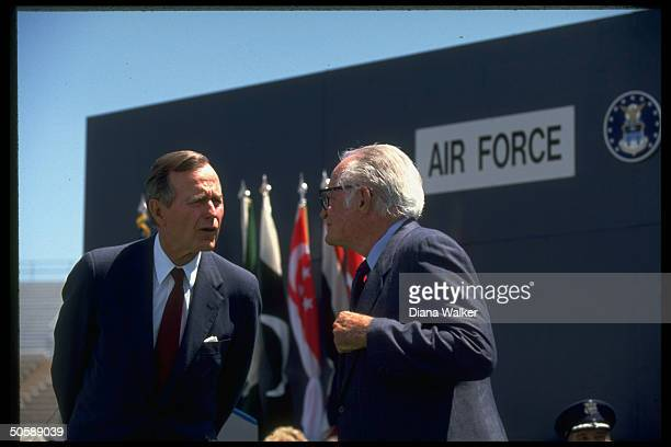 Pres Bush frowning skeptically while chatting up exSen Barry Goldwater during Air Force Academy Falcon Stadium graduation fete