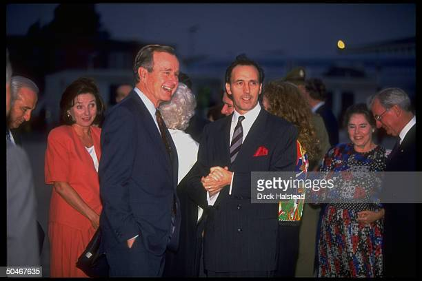 Pres Bush greeting PM Paul Keating framed by schmoozing entourage during arrival fete on 1st leg of Bush's 12day AsianPacific tour