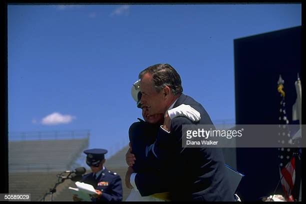 Pres Bush having high old time embracing female graduate at Air Force Academy Falcon Stadium commencement ceremony