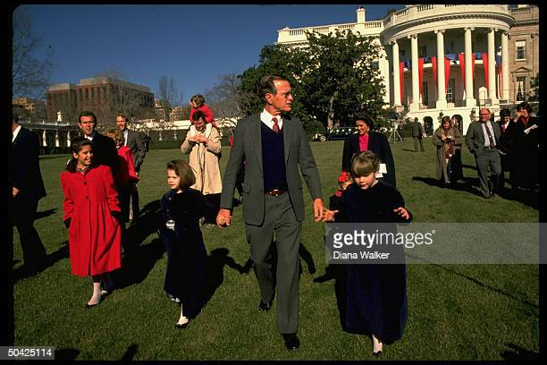 Pres Bush holding hands w granddaughters w sons spouses Margaret Marvin Neil Sharon George progeny in tow feting inaugural on WH lawn