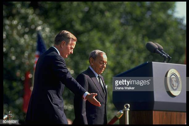 Pres. Bush hosting King Hassan of Morocco, showing him where to stand, during WH arrival ceremony speeches.