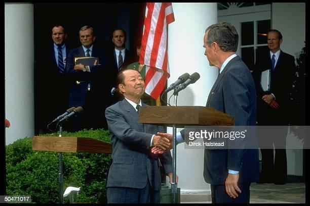 Pres Bush Japanese PM Kiichi Miyazawa shaking hands in WH Rose Garden before going to Camp David w Baker Amb Armacost Nick Brady