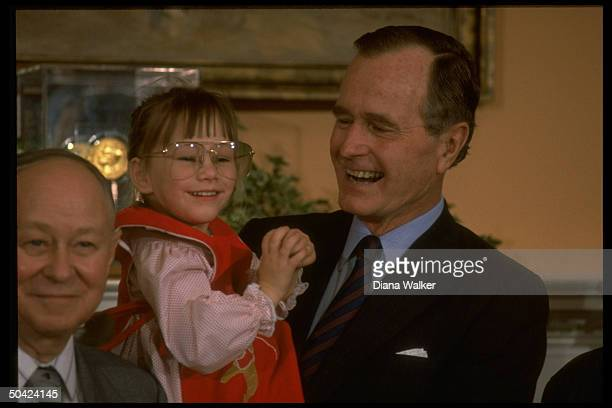 Pres Bush laughing it up w Jessica McClure Midland TX child rescued fr well holding her as she clowns wearing his glasses at WH