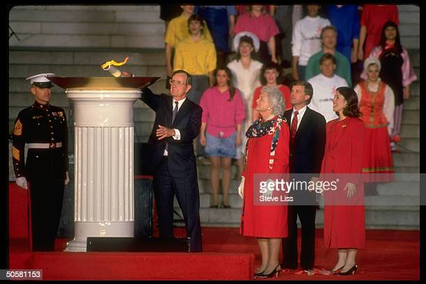 Pres Bush lighting eternaltype flame as wife Barbara VP Marilyn Quayle look on during inaugural opening ceremony at Lincoln Memorial