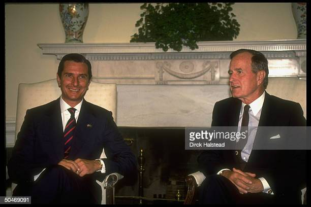 Pres Bush mtg w Brazil's Pres Fernando Collor de Mello sitting framed by WH Oval Office Swedish ivy planttopped fireplace