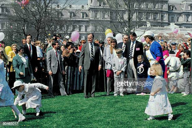 Pres Bush playing whistle master hosting WH lawn easter egg roll w granddaughter Marshall in game actor Christopher Reeve