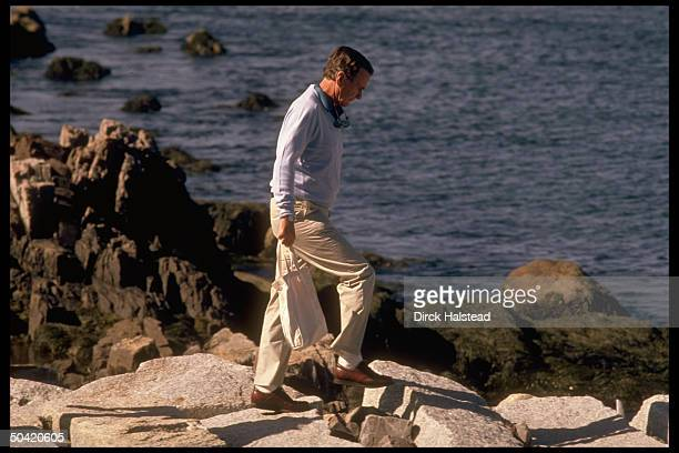 Pres Bush poised pensively on rocks overlooking water carrying tote bag