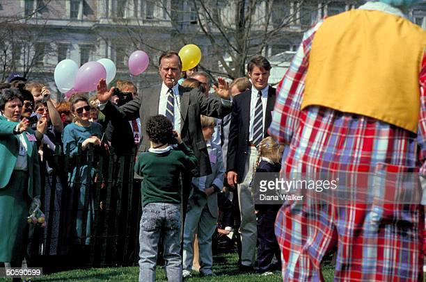 Pres Bush posing for wee photographer amid WH Easter invitees incl actor Christopher Reeve on balloonfestive WH lawn