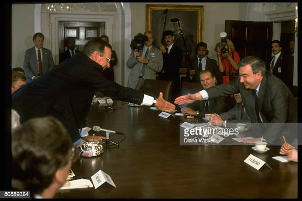 Pres. Bush reaching over table to shake hands w. Soviet Mideast envoy Yevgeny Primakov, mtg. In WH Cabinet Rm.