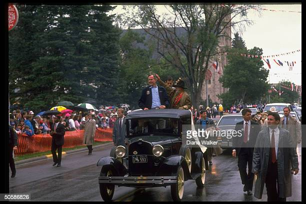 Pres. Bush riding in open antique car w. Timber Jack Lynde, during WY Centennial parade, w. Secret servicemen walking alongside.