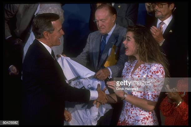 Pres Bush shaking hands w Brooke Shields w Bob Hope among cast during taping of USO 50th anniv TV special Welcome Home America