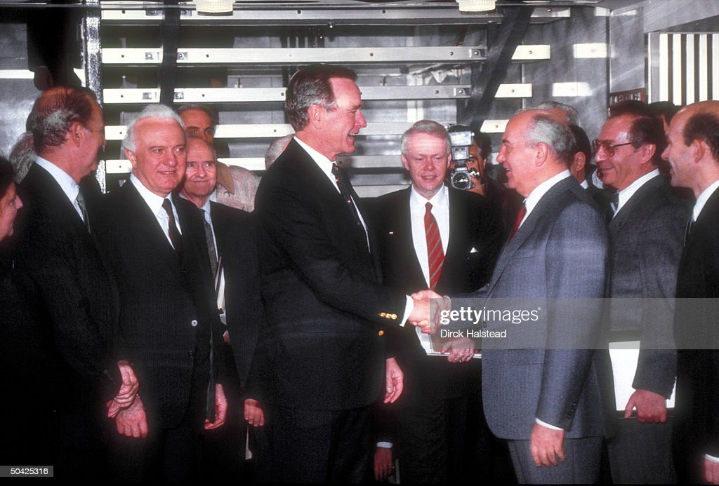 Pres. Bush (C) shaking hands w. Soviet Pres. Gorbachev as (R-L) aides Palazhenko, Bessmertnykh, interpreter, Scowcroft, Shevardnadze & Baker look on, during summit.
