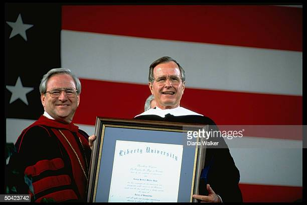Pres Bush sporting academic robes proudly displaying his honorary degree w Rev Jerry Falwell at Liberty Univ graduation ceremony