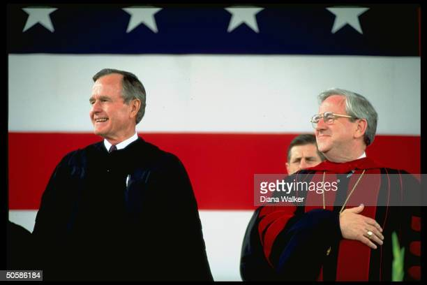 Pres Bush sporting academic robes w handoverheart poised Rev Jerry Falwell at Liberty Univ graduation ceremony