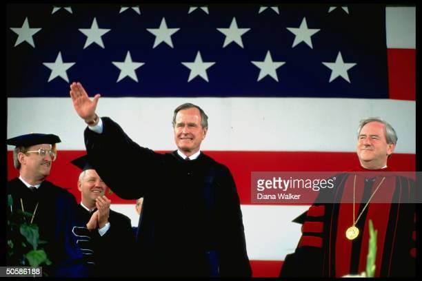 Pres Bush sporting academic robes waving w Rev Jerry Falwell school officials at Liberty Univ graduation ceremony