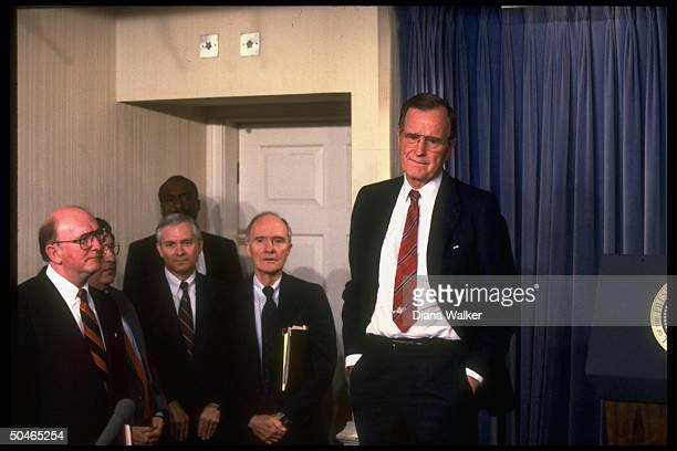 Pres Bush striking pensive lipbiting stance in WH Press Rm w attentive aides Fitzwater Sununu Gates Scowcroft