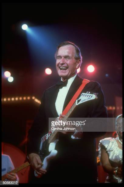 Pres Bush strutting his stuff w personalized electric guitar having high old time at TXstyle black tie boots inaugural ball