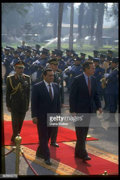 Pres Bush treading red carpet w Pres Mubarak reviewing troops at arrival fete here on gulf crisis business