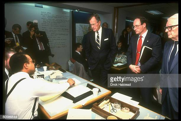 Pres. Bush visiting office of emergency coordination agency FEMA, questioning staffers on response to earthquake.