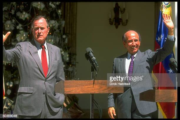 Pres Bush w Pres Carlos Andres Perez poised waving at twin podiums during news conf outside pres palace in Caracas Venezuela
