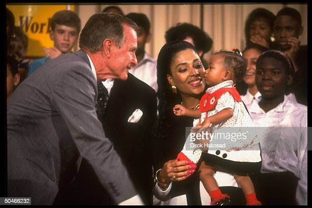 Pres Bush w track star mom Flo Jo Griffith Joyner cooing at baby Mary paying call at Alice Deal Jr HS
