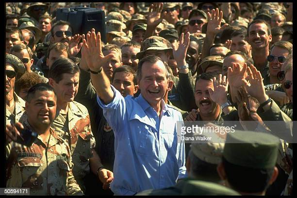 Pres Bush waving framed by admiring crowd of soldiers just 1ofboys spending Thanksgiving in desert w US gulf crisis troops