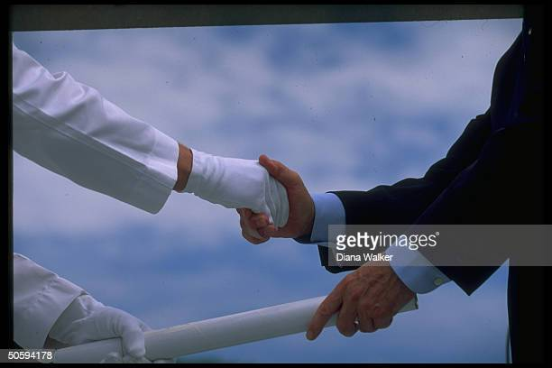Pres Bush's handsinmotion presenting graduating cadet w diploma shaking whitegloved hand at West Point commencement ceremony