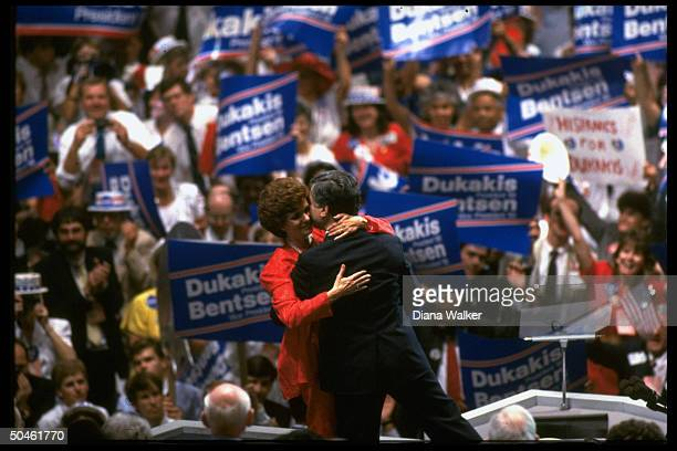 Pres cand Gov Michael Kitty Dukakis hugging against backdrop of sign waving supporters on floor of Dem Natl Convention