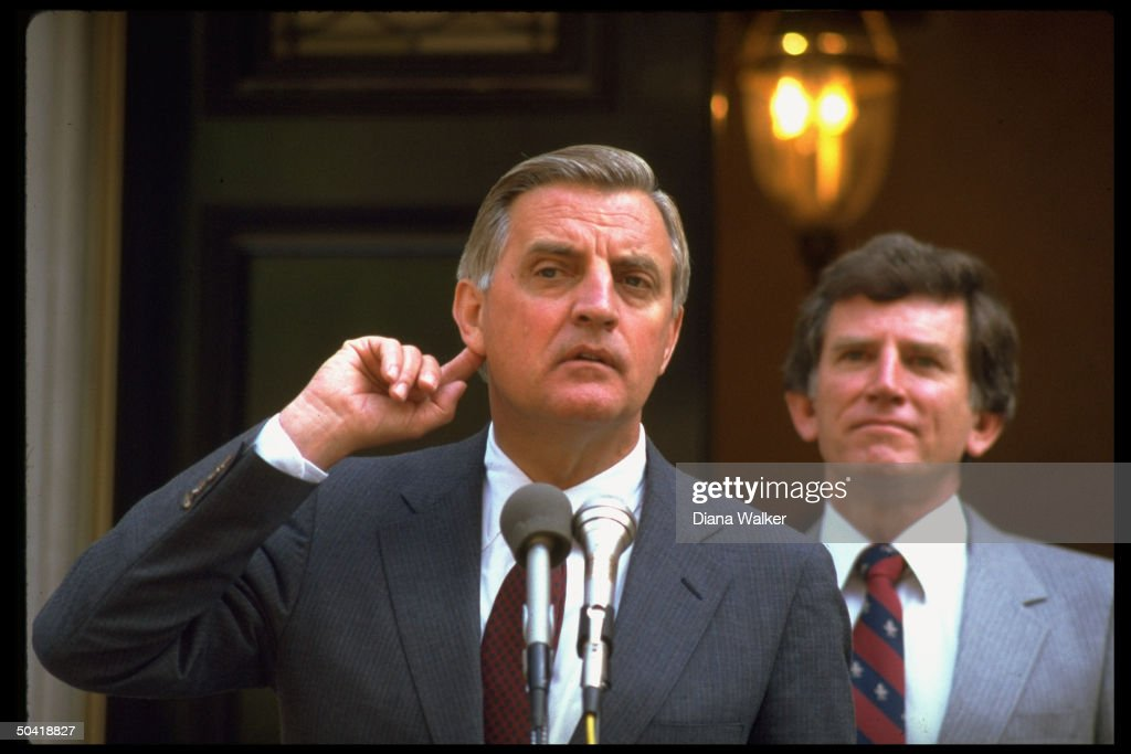 Pres. cand. Walter Mondale (C) w. finger to ear, w. Sen. Gary Hart (L) at press conf. after they met privately.