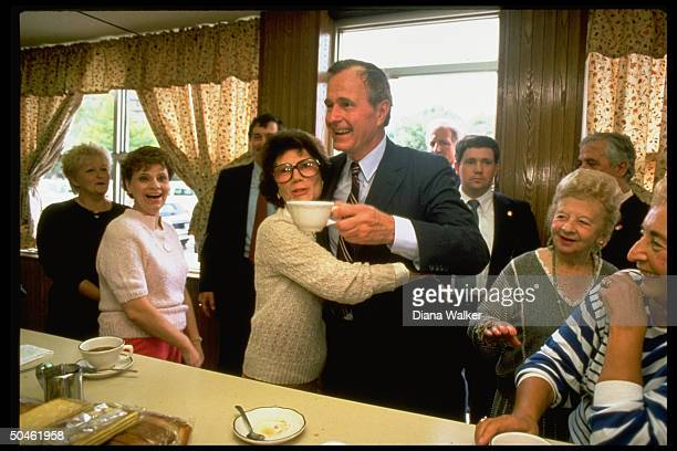 Pres cand/VP George Bush w coffee cup being embraced by woman prob in diner