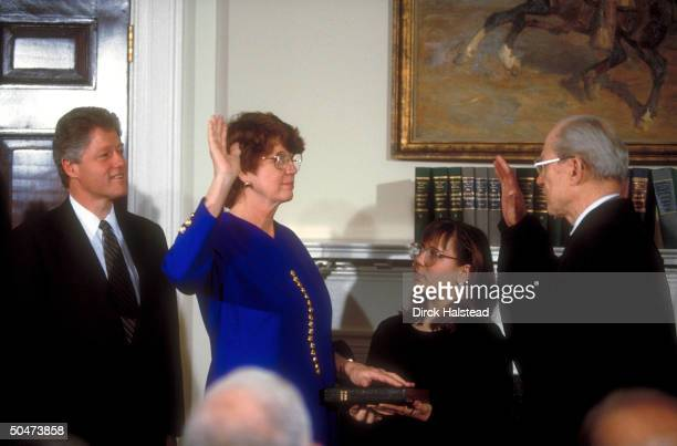 Pres Clinton looking on as Supreme Court Justice Byron White swears in Atty Gen Janet Reno w Reno's niece Janet holding Bible