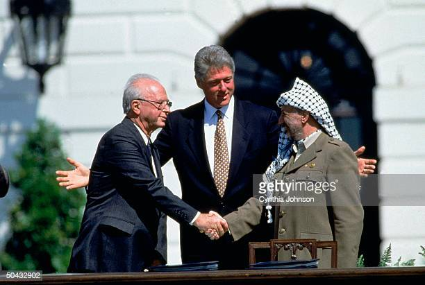 Pres Clinton smiling as PLO chmn Arafat Israeli PM Rabin seal signing of IsraelPLO peace accord w historic handshake at White House