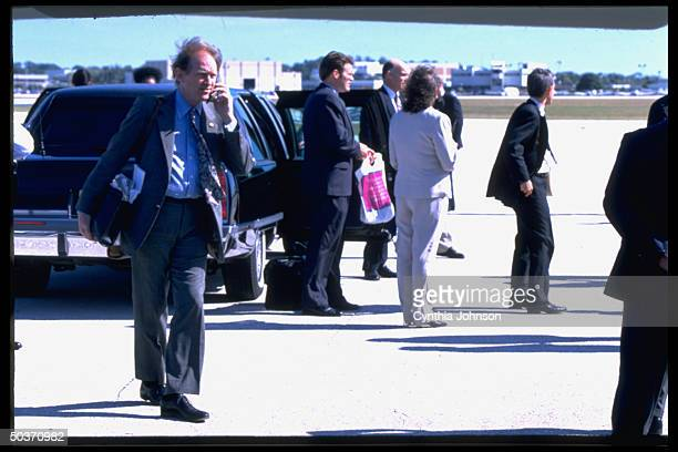 Pres. Clinton's deputy chief of staff Harold Ickes taking call on cellular phone, poised by presidential limo on airport tarmac.
