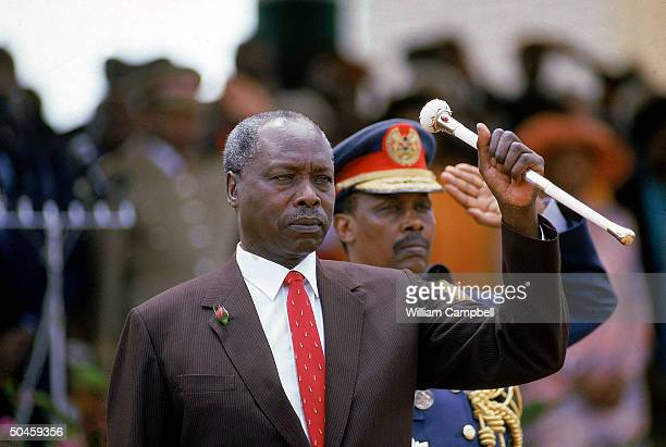 Pres Daniel Arap Moi poised w baton assuming serious stance during his 4th term inaugural ceremony w Chief of Staff Mohammed in rear