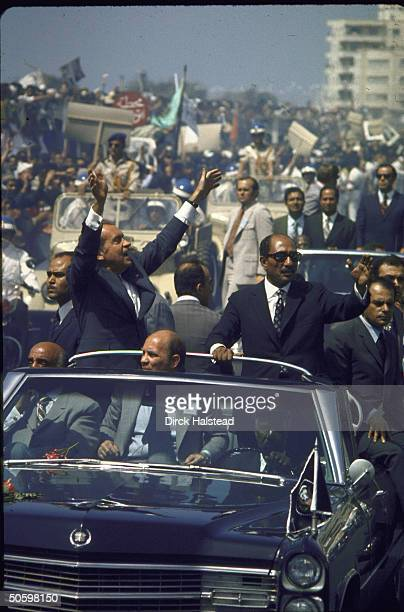 US Pres Dick Nixon his host Pres Anwar Sadat riding in open car through crowdlined motorcade route in Cairo Egypt