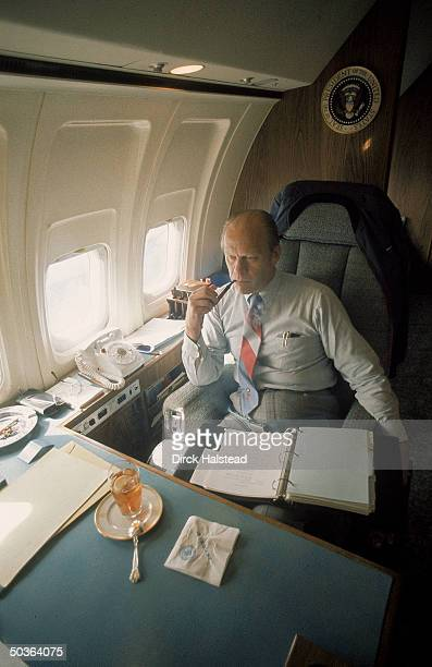 Pres Ford reading notebook on his lap aboard the Air Force One between Las Vegas Phoenix