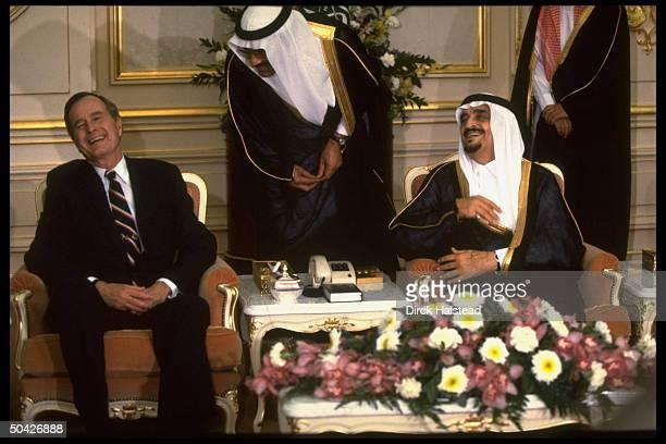 Pres George Bush laughing during mtg w Saudi King Fahd w interpreter between during diplomatic tour during gulf crisis