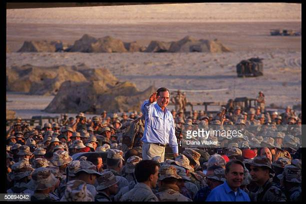 Pres George Bush poised waving above crowd of First Marine Division desert command post marines spending Thanksgiving w American troops on gulf...