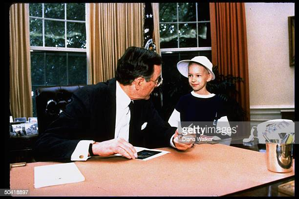 Pres George Bush signing autograph for young cancer patient Ginny Bruington standing w Bush at his desk in Oval office