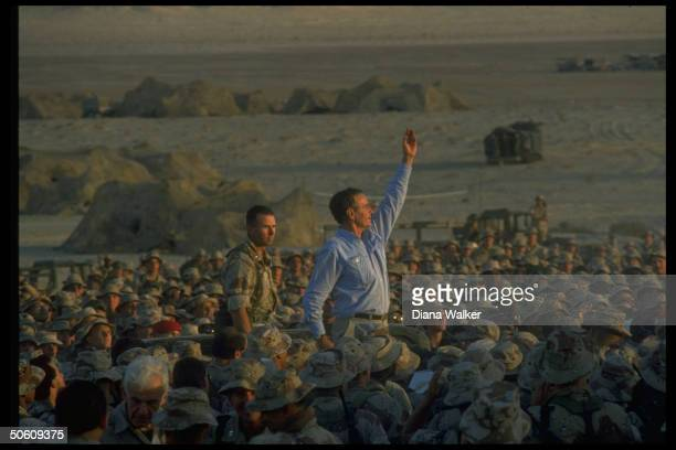 Pres George Bush waving triumphantly above crowd of First Marine Division desert command post marines spending Thanksgiving w American troops on gulf...