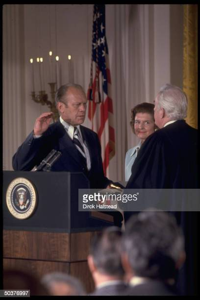 Pres Gerald Ford taking oath of office being swornin by Chief Justice Warren Burger w wife Betty between them hours after Pres Nixon resigned