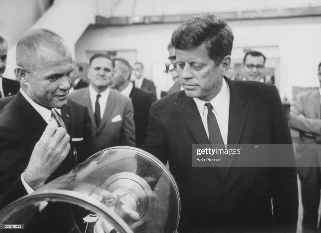 Pres. John Kennedy (R) trying on a space glove as astronaut John Glenn explains its use, during his inspection tour of the Manned Space Center.