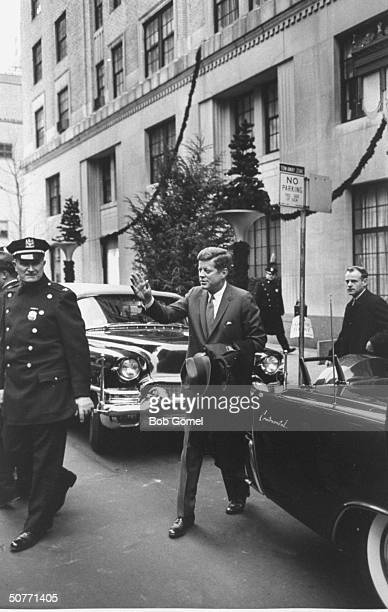 Pres John Kennedy waving as he leaves the Carlyle Hotel at 230 pm under the watchful eye of a police officer as he heads for the Economic Club dinner...