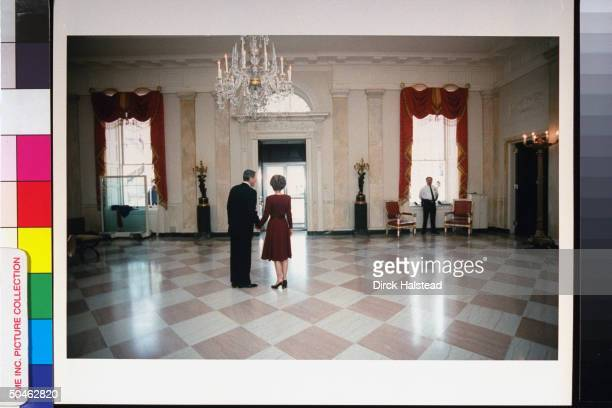 Pres Nancy Reagan standing handinhand turning for last look out around WH rm on their final day in residence after 8 yrs in office