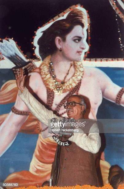 Pres of Bharatiya Janata Party Hindu a nationalist Hindu group L K Advani speaking in front of large poster of Hindu god Rama w hand raised
