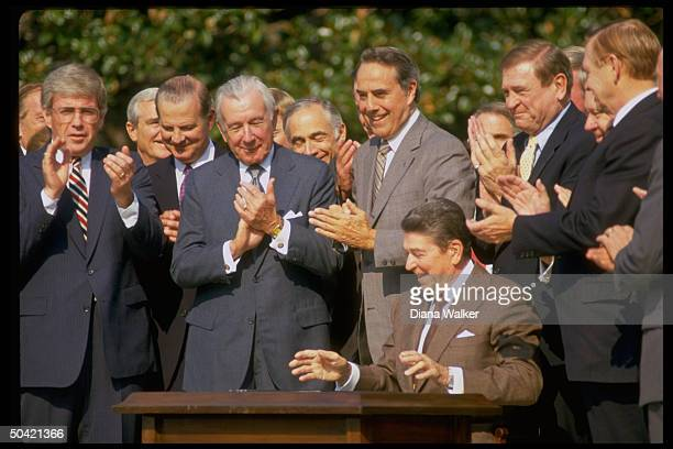 Pres Reagan applauded by Rep Kemp aides Baker Regan Sen Dole Rep Rostenkowski during Tax Reform Bill signing ceremony at WH