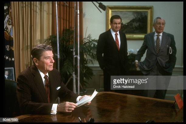 Pres Reagan holding notes in Oval Office w aides Don Regan Pat Buchanan after TV speech on arms shipments to Iran